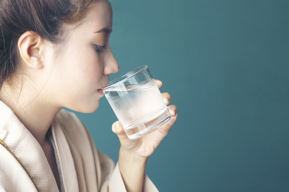 Scandinavian woman drinks water after sauna